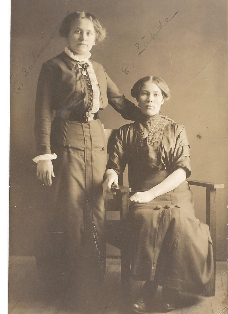 Woman standing, woman sitting.